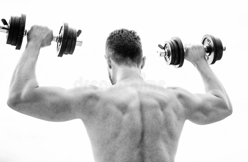 Muscular man exercising with dumbbell rear view. Actions speak louder than coaches. Sportsman with strong back and arms stock images