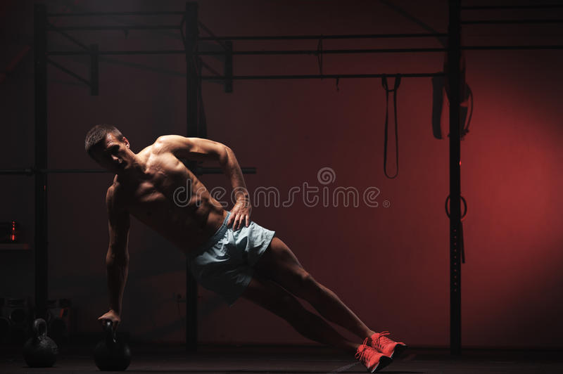 Muscular man exercising with kettle bell in gym stock image