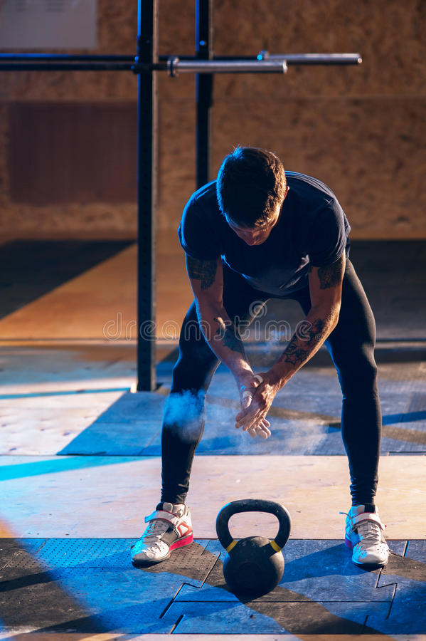 Muscular man exercising with kettle bell in gym stock photo