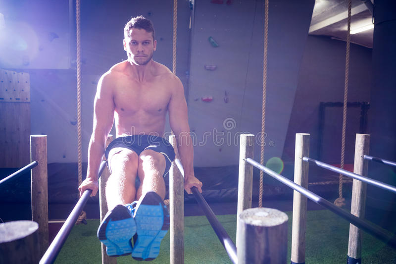 Muscular man exercising on parallel bars. In crossfit gym stock images