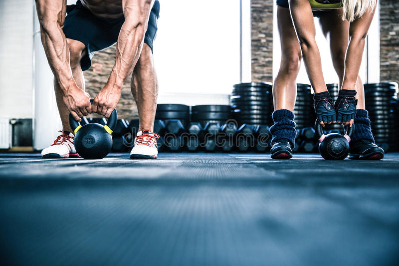Muscular man and fit woman workout with kettle ball. Muscular men and fit women workout with kettle ball at gym stock image