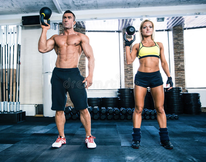 Muscular man and fit woman workout with kettle ball. Muscular men and fit women workout with kettle ball at gym royalty free stock photo