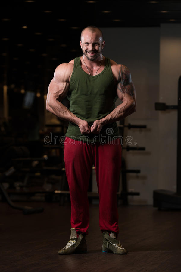 Muscular Man Flexing Muscles In Gym royalty free stock image