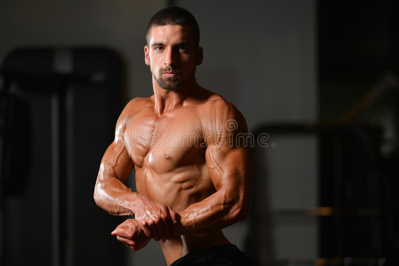 Muscular Man Flexing Muscles In Gym. Portrait Of A Young Physically Fit Man Showing His Well Trained Body - Muscular Athletic Bodybuilder Fitness Model Posing stock images