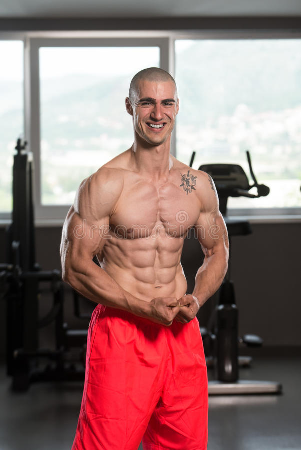 Muscular Man Flexing Muscles In Gym. Young Man Standing Strong In The Gym And Flexing Muscles - Muscular Athletic Bodybuilder Fitness Model Posing After stock photos