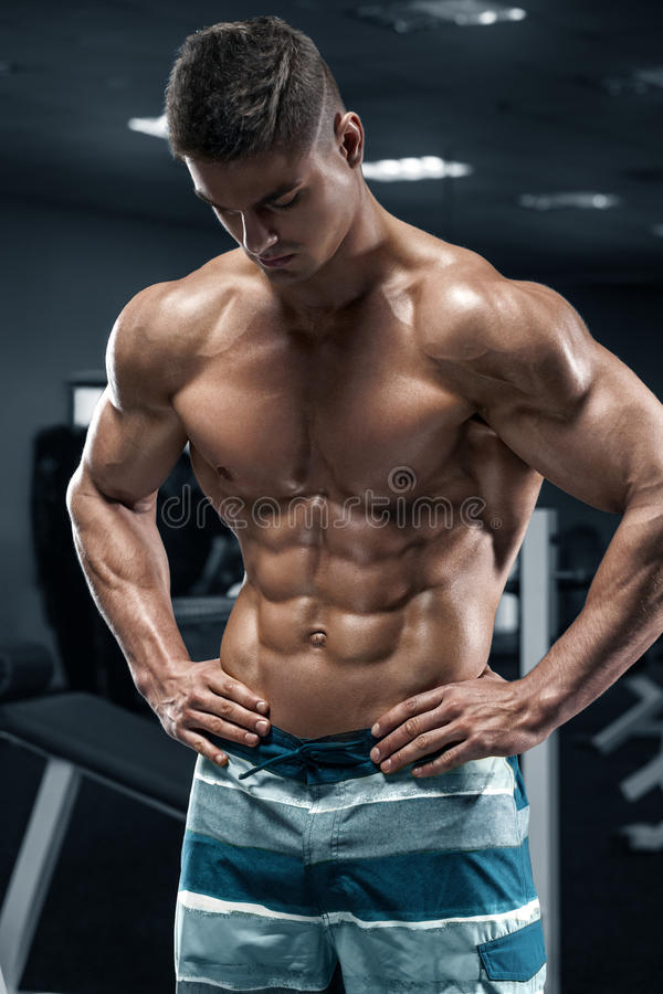 Muscular man in gym, abs, working out. Strong male naked torso, shaped abdominal stock photography