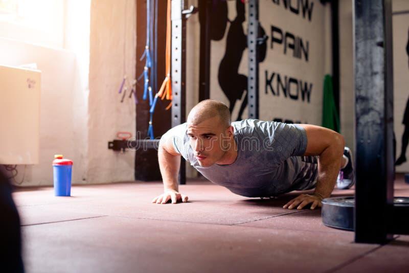 Man in gym doing push ups. Muscular man in gym doing push ups stock images