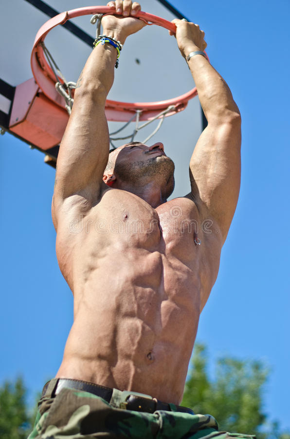 Muscular man hanging from basketball ring stock photo