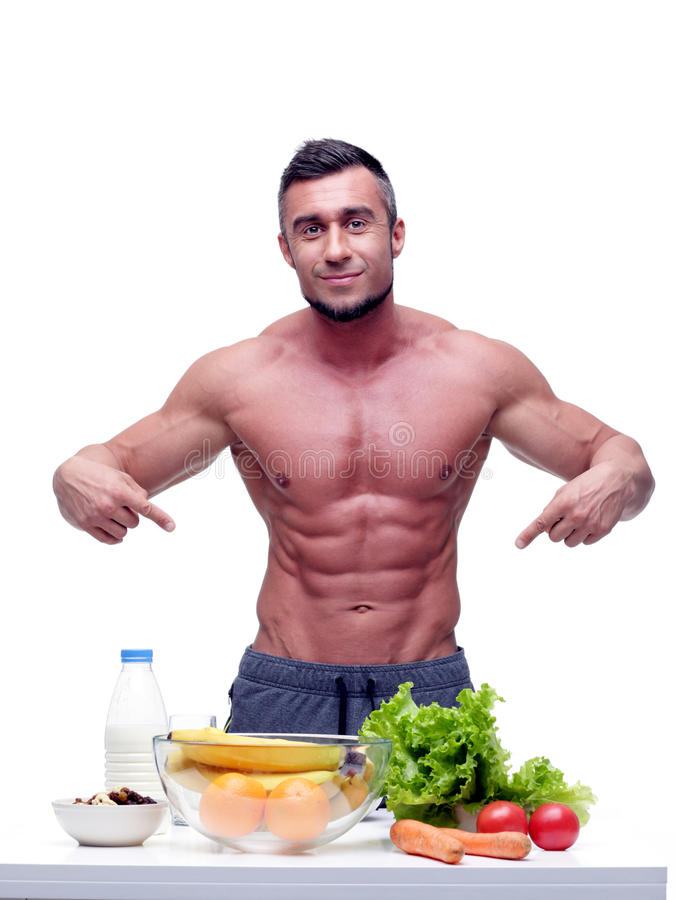 Muscular man with healthy food. Portrait of a handsome muscular man with healthy food stock image