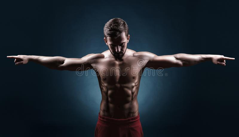 Muscular man. Healthy muscular young man showing his muscles against a dark background stock photos
