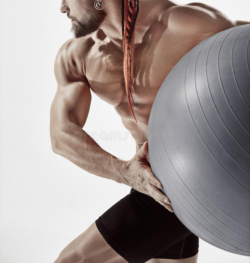 Muscular man holding fitness ball, standing isolated on white stock photo