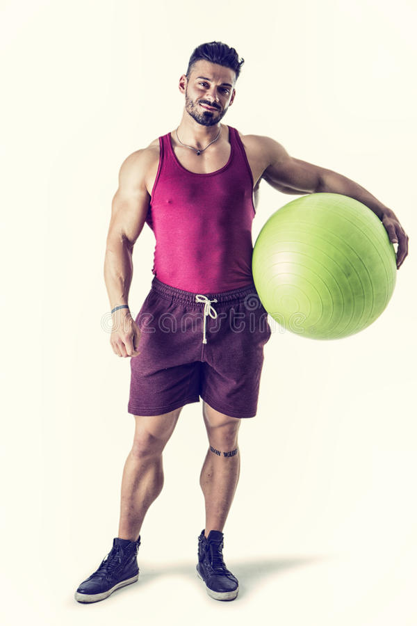 Muscular man holding inflatable fitness ball royalty free stock image