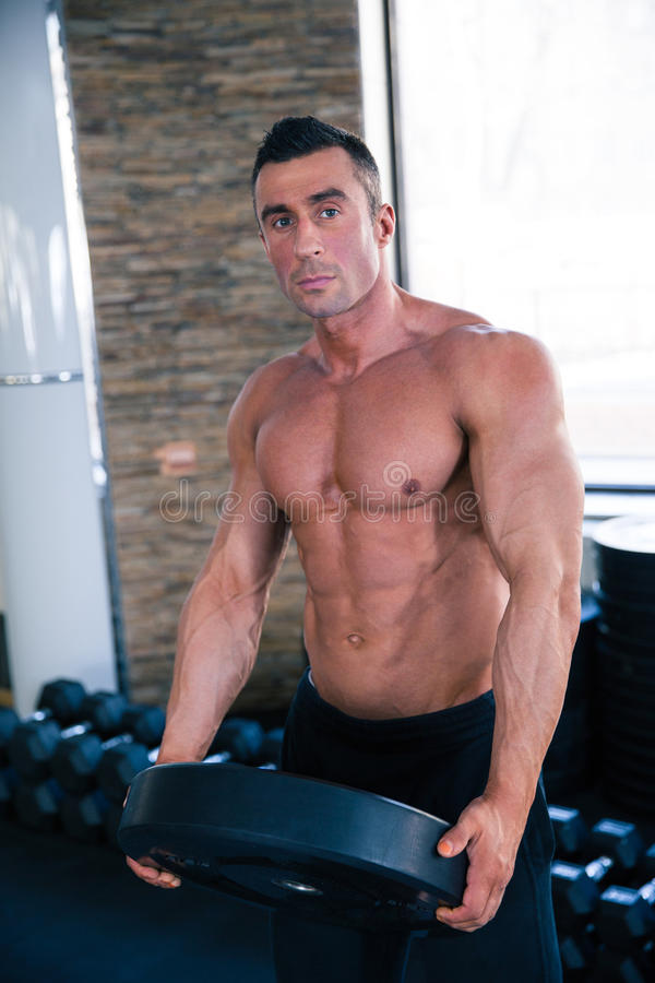 Muscular man holding weight and looking at camera royalty free stock image