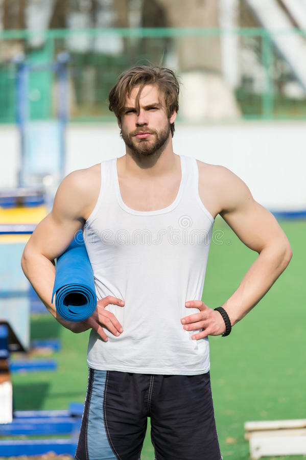 Muscular man holding yoga or fitness mat for exercise stock images