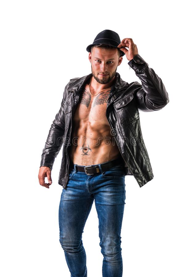 Muscular man with jacket on naked torso. Muscular man with leather jacket on naked torso, wearing fedora hat, isolated on white background in studio stock photos