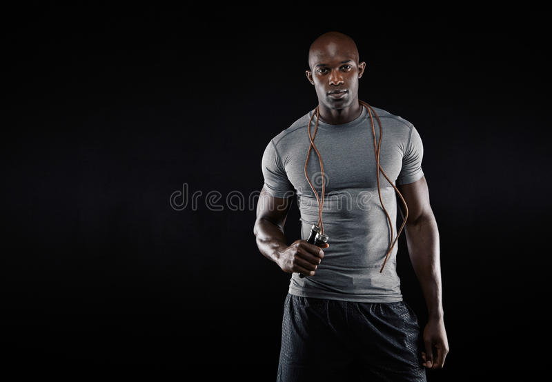 Muscular man with jumping rope. Studio shot of young african muscular man with jumping rope against black background. Fitness model with skipping rope around his stock photo
