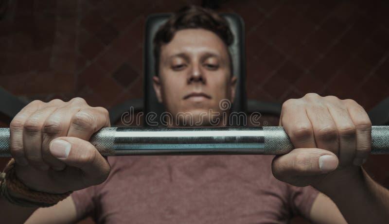 Muscular man lifting a barbell royalty free stock photo