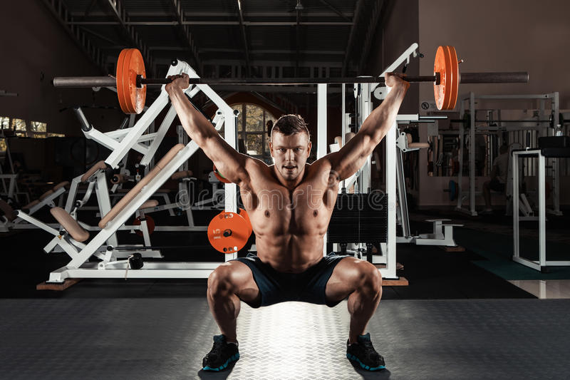 Muscular man lifting a barbell royalty free stock photography