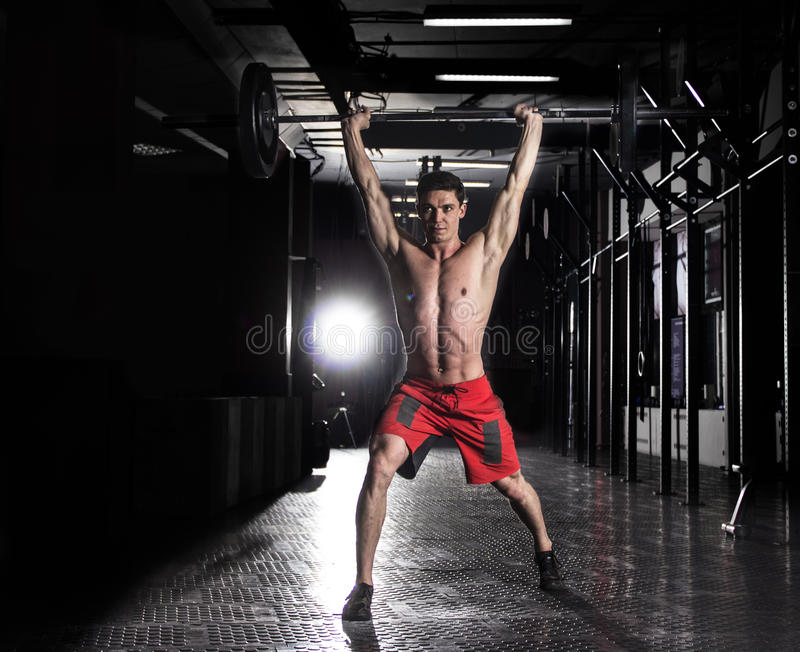 Muscular man lifting a barbell in crossfit gym. stock images