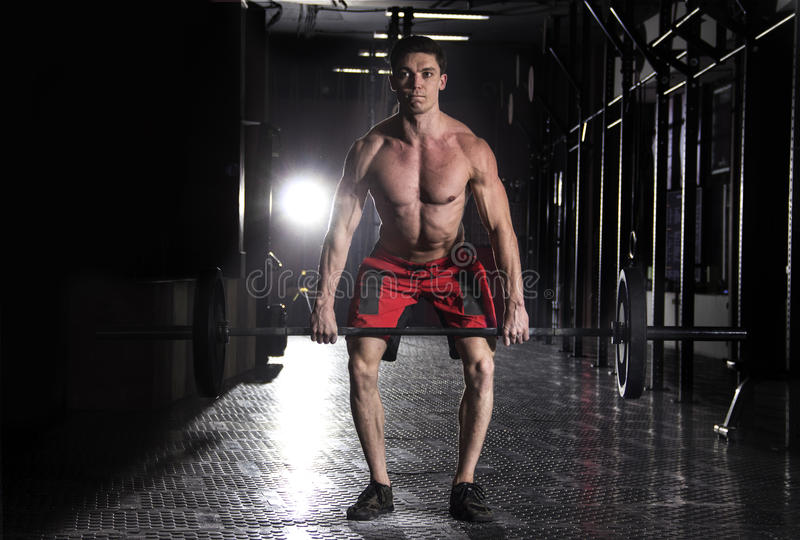 Muscular man lifting a barbell in crossfit gym. stock photo