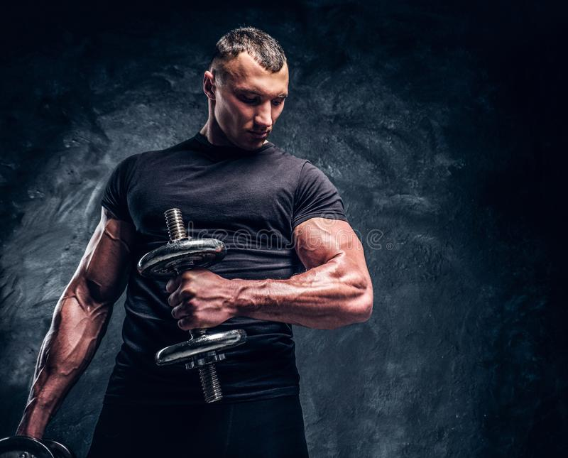 Muscular attractive bodybuilder lifting a barbell stock images