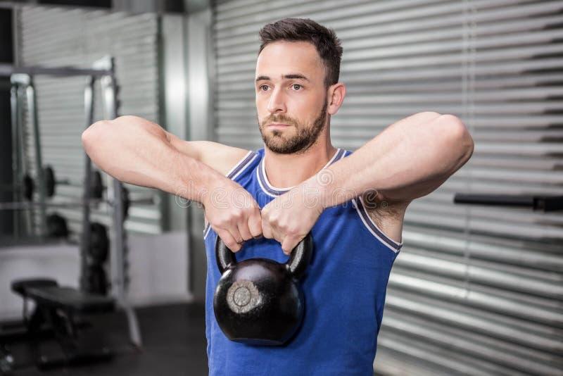 Muscular man lifting heavy kettlebell stock photos