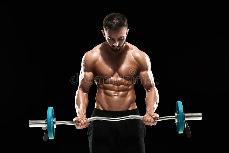 Muscular man lifting weights over dark background royalty free stock photo