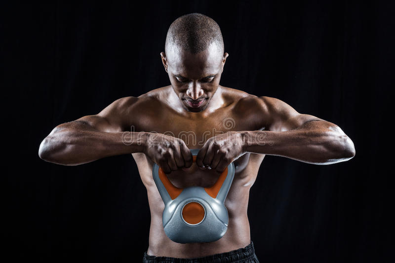 Muscular man looking down while exercising with kettlebell stock photography