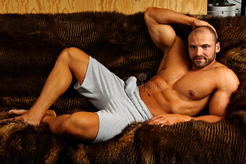 Muscular man lying. On couch and relaxes royalty free stock photo