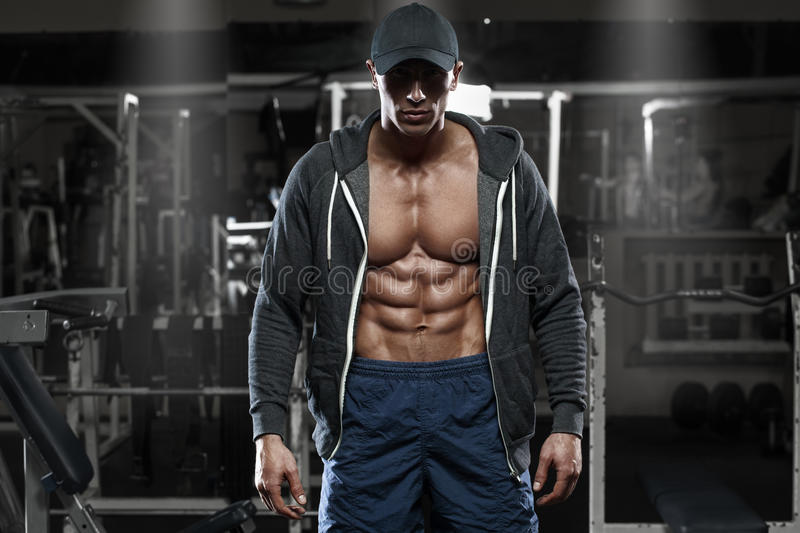 Muscular man with open jacket revealing chest and abs in gym, workout stock images