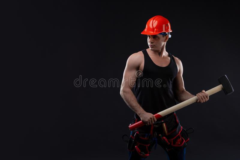 Muscular man in orange helmet with great anatomy posing on a black background with a big hummer in his hands. stock photos