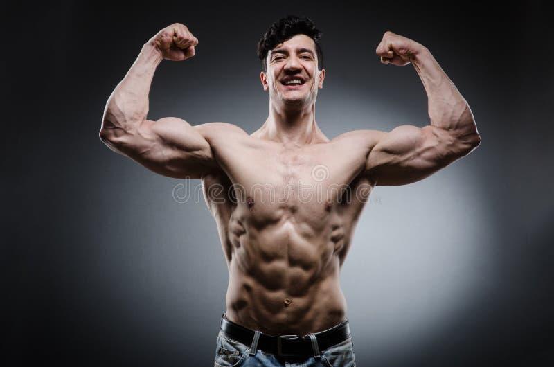 Muscular man posing in dark studio. The muscular man posing in dark studio stock photography