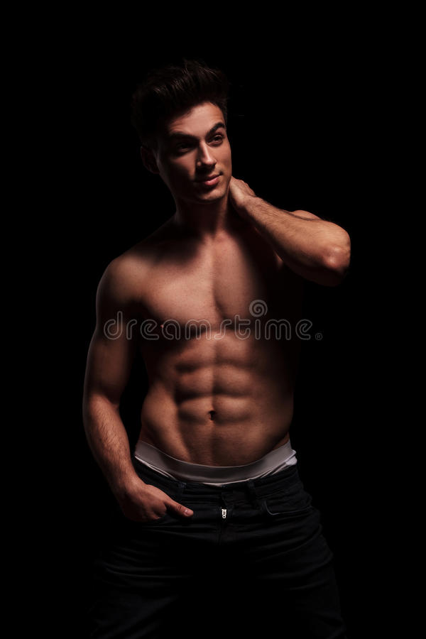 Muscular man posing with hand in pocket stock photo