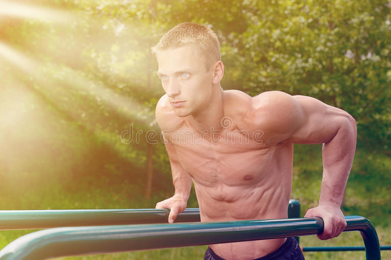 Muscular man practice street workout in an outdoor gym royalty free stock images