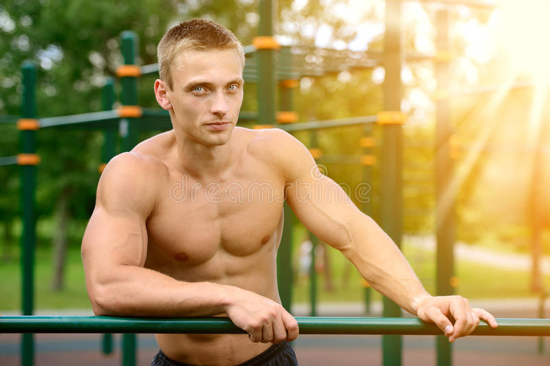 Muscular man practice street workout in an outdoor gym royalty free stock photos