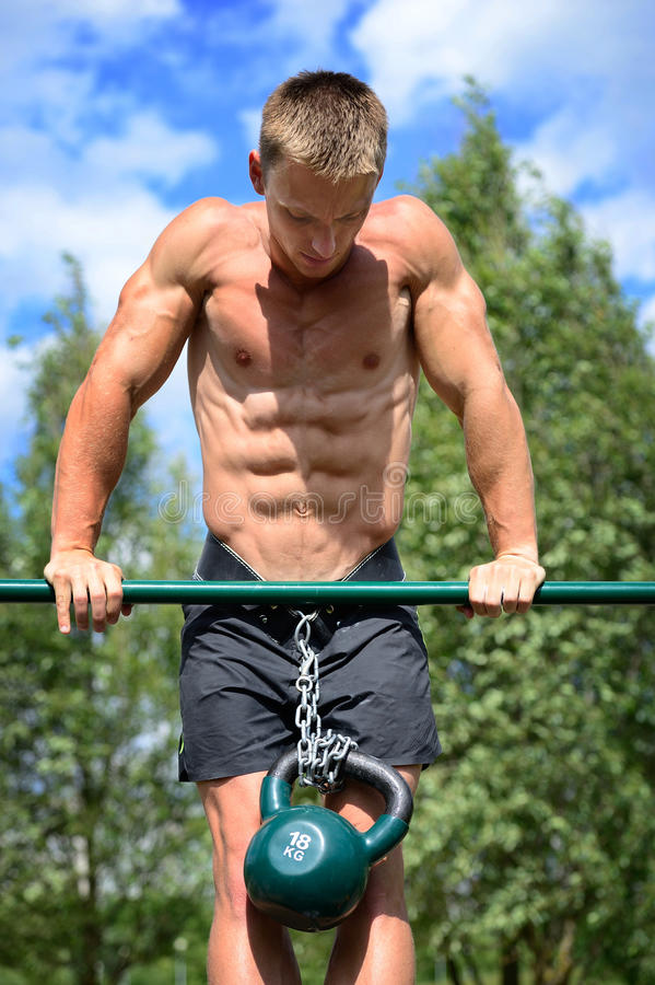 Muscular man practice street workout in an outdoor gym royalty free stock image