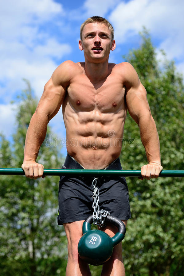 Muscular man practice street workout in an outdoor gym stock photography