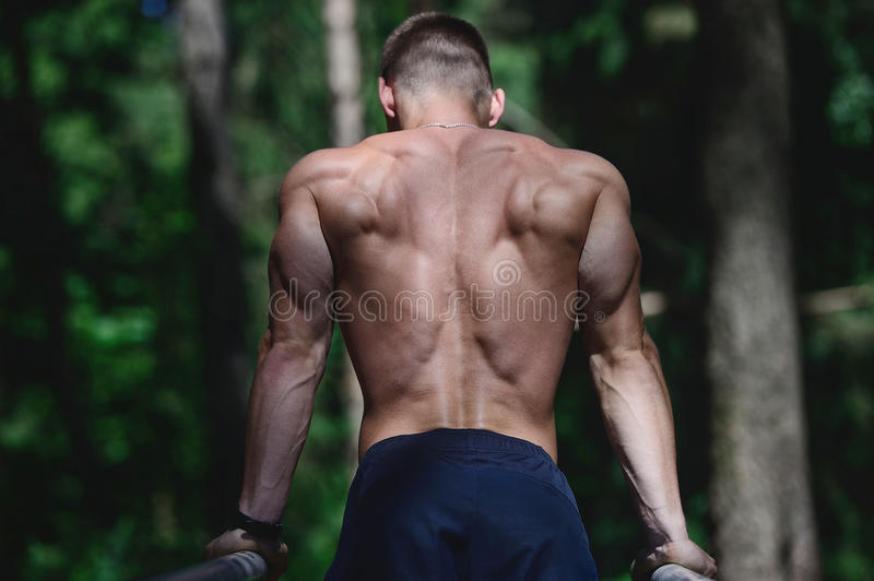 Muscular man practice street workout in an outdoor gym stock images