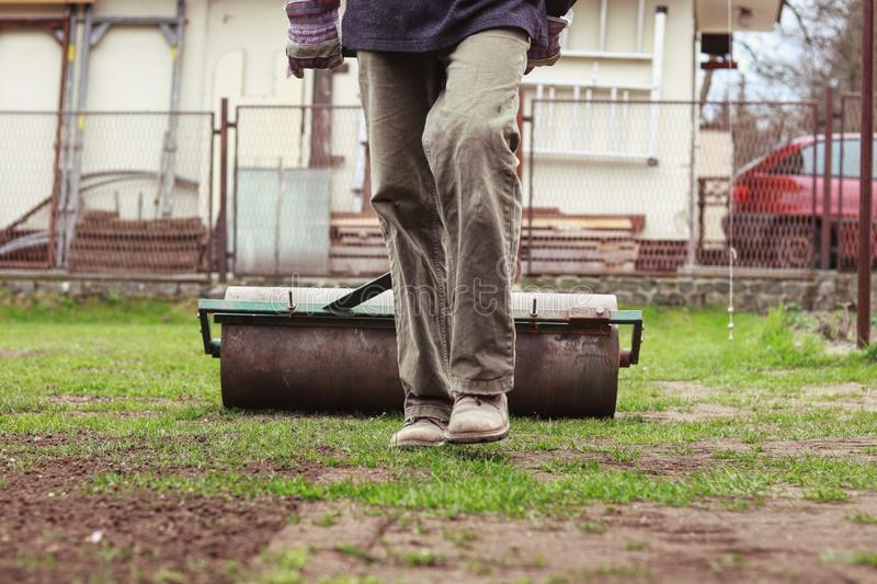 Muscular man pulls heavy lawn roller behind and trying give garden on same level without holes. Necessary maintenance for stock photography