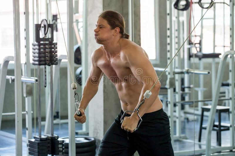 Muscular man pumping up muscles chest with cable crossover at gym in morning light .workout , exercises , bodybuilder training , stock photography