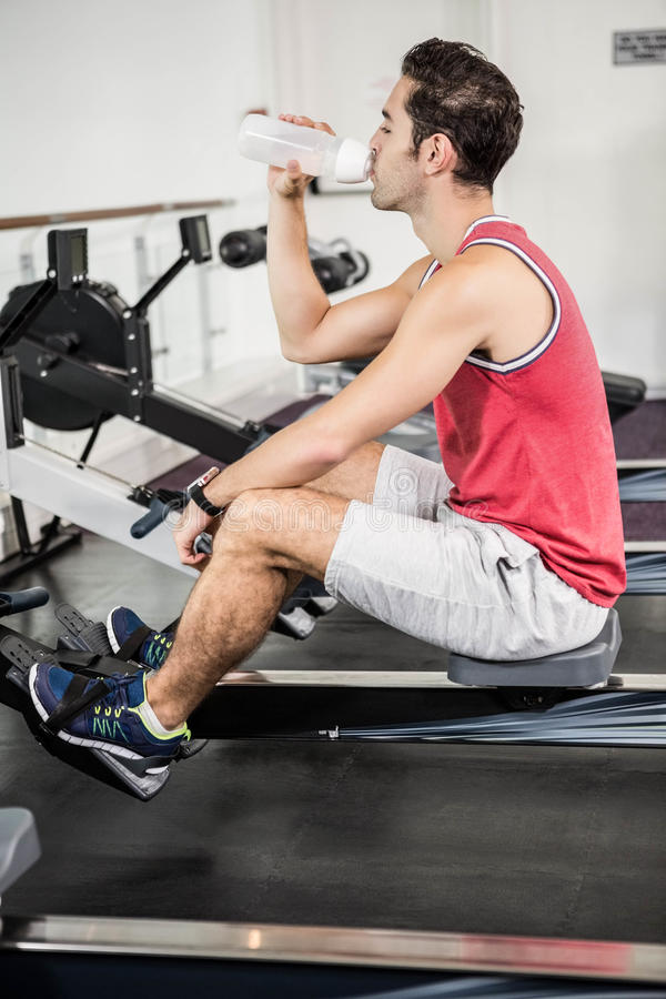 Muscular man on rowing machine drinking water royalty free stock photography