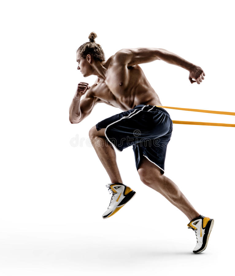 Muscular man runner in silhouette using a resistance band in his exercise routine. stock image