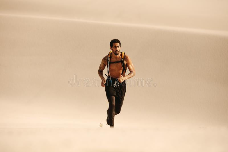 Muscular man running on sand dunes stock images