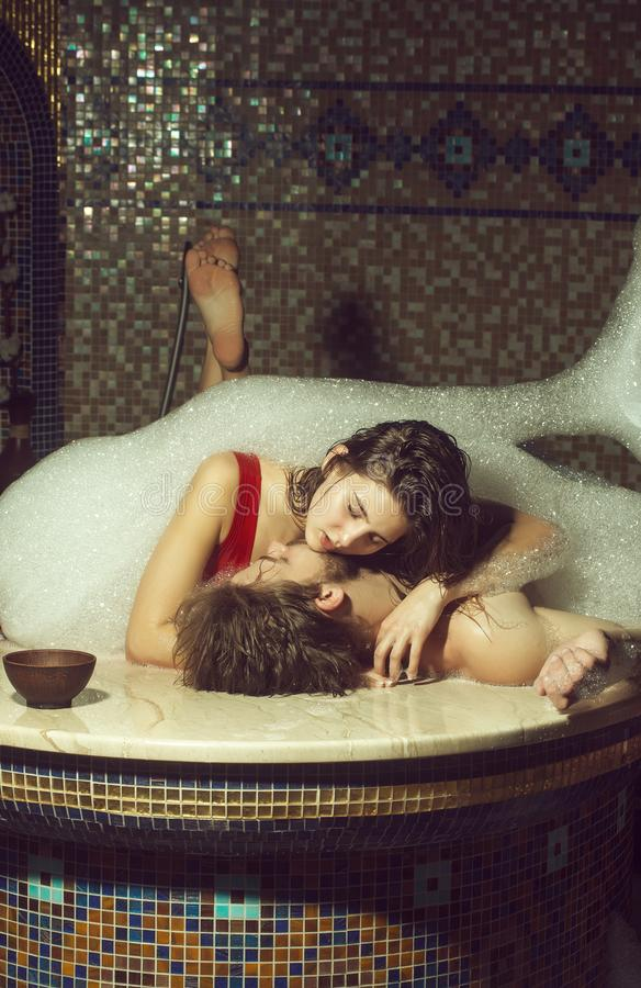 Muscular man and woman laying in bath with foam royalty free stock photography