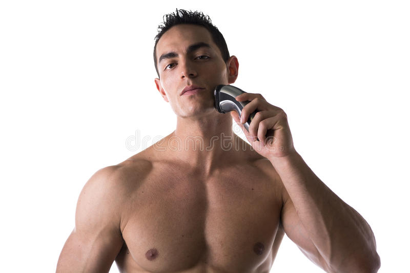 Muscular man shirtless using electric shaver. Looking at camera, isolated on white stock images