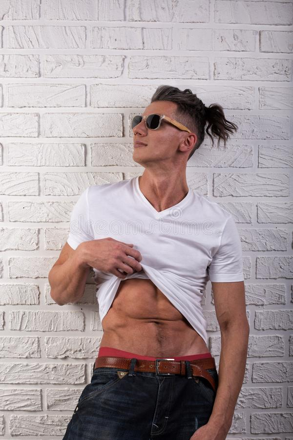 A muscular man showing his abs on white background.  stock images