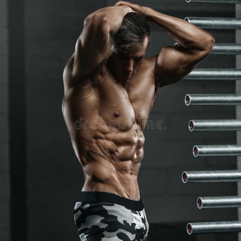 Muscular man showing muscles, posing in gym. Strong male naked torso abs, working out.  stock photography