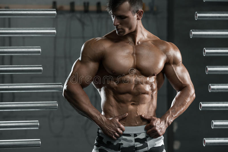 Muscular man showing muscles, posing in gym. Strong male naked torso abs, working out.  stock photo