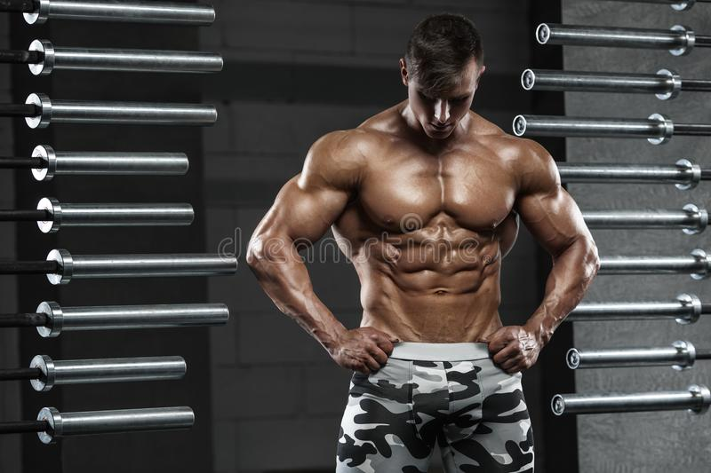 Muscular man showing muscles, posing in gym. Strong male naked torso abs, working out royalty free stock image