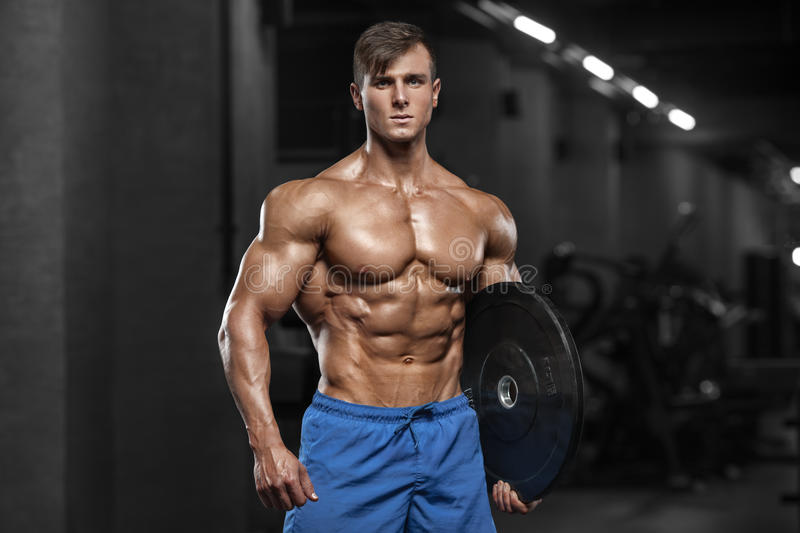 Muscular man showing muscles, posing in gym. Strong male naked torso abs, working out stock images
